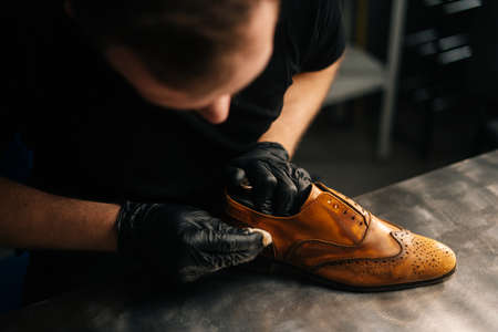 Top close-up view of professional shoemaker wearing black gloves polishing old light brown leather shoes. Concept of cobbler artisan repairing and restoration work in shoe repair shop.