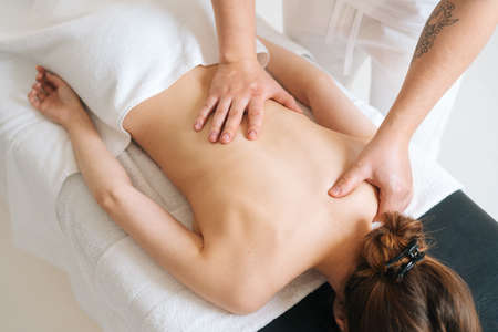 Top view of male masseur doing back massage to young unrecognizable woman in spa salon. Professional physiotherapist with strong hands making movements with hand along the spine toward head.
