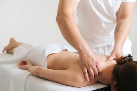 Male masseur with strong hands professionally massaging scapulas and shoulders to female client. Beautiful young woman with perfect skin getting relaxing back massage at spa salon.