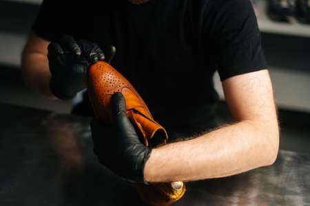 Close-up hands of shoemaker wearing black gloves rubbing paint on toe cup of light brown leather shoes with fingers. Concept of cobbler artisan repairing and restoration work in shoe repair shop. Stock fotó