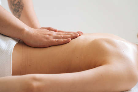 Side view of male masseur massaging small of back of young woman lying on massage table at light spa salon. Experienced chiropractor performs wellness treatments for lady with back pain.