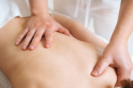 Top view of hands of male masseur with strong hands professionally massaging scapulas and shoulders. Beautiful young woman with perfect skin getting relaxing massage. Stock Photo