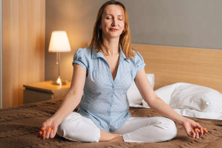 Portrait of smiling peaceful woman relaxing on lotus position sitting on bed in cozy bedroom with closed eyes. Young female practicing meditation at home. Concept of leisure activity at home.