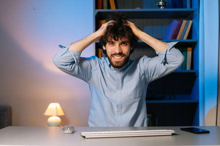 Front view of crazy young man pulling hair on head sitting at desk with computer at home office, looking at camera. Smiling happy bearded guy showing eureka gesture. Concept of remote working.