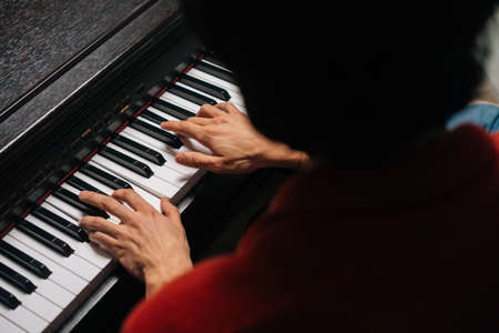 Top close-up view of hands of unrecognizable musician man playing on piano at home. Closeup back view fingers of pianist male playing digital electronic piano synthesize. Concept of music education. Stock fotó