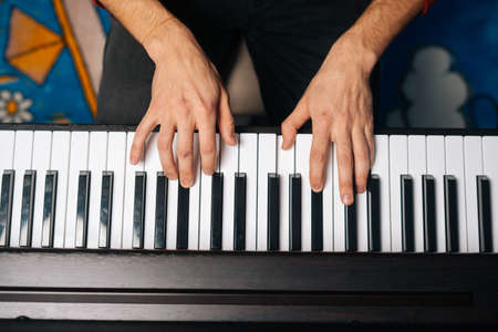 Top close-up view of hands of unrecognizable man playing on piano at home. Closeup view fingers of male playing digital electronic piano synthesize. Concept of music education. Stock fotó