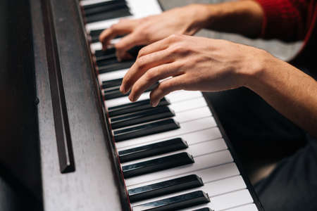 Close-up hands of unrecognizable man playing on piano at home recording studio. Closeup side view fingers of male playing digital electronic piano synthesize. Concept of music education.