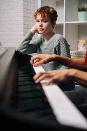 Focused redhead child student boy listening his teacher play the piano during lesson and looking at camera. Father teaching son to play musical instrument in living room. Concept of music education.
