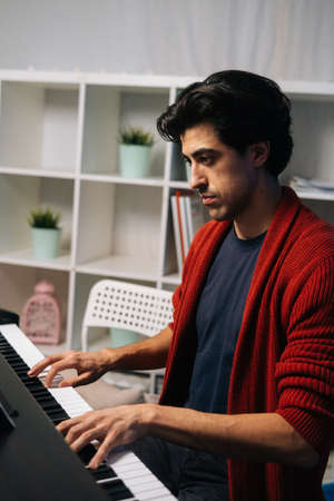 Side view of focused young musician man playing piano at home studio during lesson in free time. Guy practicing piano lesson looking on musical notes in living room. Concept of music education.