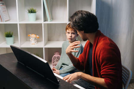 Caucasian boy playing synthesizer at home during lesson. Loving dad teaching talented son to play musical instrument in living room. Concept of music education. Stock fotó