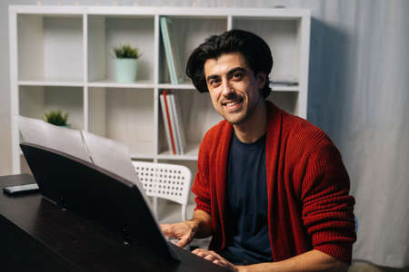 Portrait of cheerful bearded young pianist man sitting at piano and looking at camera. Male musician practicing piano lesson looking on musical notes in living room. Concept of music education.