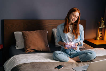 Redhead young woman holding gift box with present during online communication using laptop computer. Happy lady sitting on bed at light bedroom and using laptop, looking on display screen..