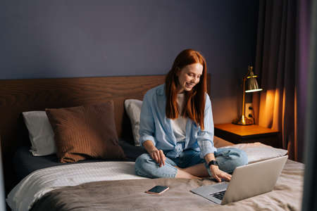Happy redhead young woman making video call on webcam at bedroom. Portrait of cheerful female having video chat on laptop at home. Smiling lady chatting online on notebook looking on display screen.