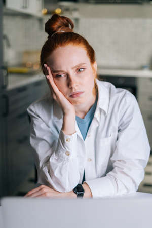 Close-up portrait of tired young redhead woman sitting at desk in cozy living room. Concept of leisure activity red-haired female at home during self-isolation. Stock fotó