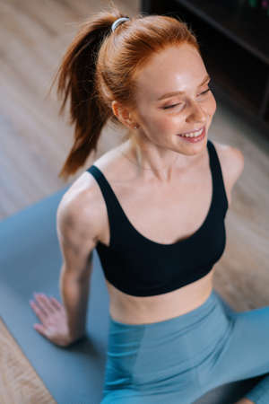 High-angle view of cheerful redhead young woman wearing sportswear sitting in floor on yoga mat, looking away. Concept of sports training red-haired lady during quarantine. Stock fotó