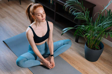 Top view of calm relaxed redhead young woman meditating in lotus pose with closed eyes in floor on yoga mat. Concept of sports training red-haired lady during quarantine. Stock fotó