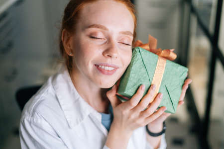 Close-up face of cheerful redhead young woman with closed eyes gently cradling surprise gift box to face at home. Concept of leisure activity red-haired female at home during self-isolation.
