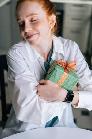 Close-up face of dreamy redhead young woman gently cradling surprise gift box to heart at home, looking away. Concept of leisure activity red-haired female at home during self-isolation.