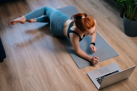 Top view of fit redhead young woman working out, doing stretching exercise on yoga mat while watching fitness video online on laptop. Concept of sports training red-haired lady during quarantine.