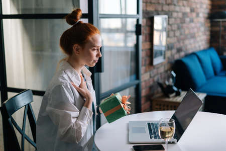Side view of smiling redhead young woman holding present gift box during video call via laptop webcam. Concept of leisure activity red-haired female at home during self-isolation. Stock fotó