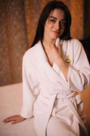 Middle shot portrait of smiling young woman in white bathrobe sitting on massage table in spa salon with soft lighting. Beautiful girl after a massage. Concept of luxury professional massage.