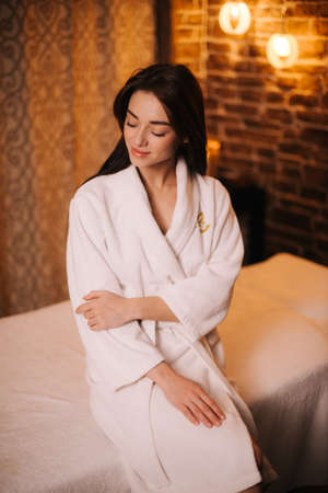 Beautiful girl in white bathrobe sitting on massage table in spa salon with soft lighting, looking away. Beautiful girl after a massage. Concept of luxury professional massage.