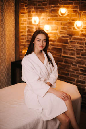 Young relaxed woman in white bathrobe sitting on massage table in spa salon with soft lighting, looking at the camera. Beautiful girl waiting for massage. Concept of luxury professional massage.