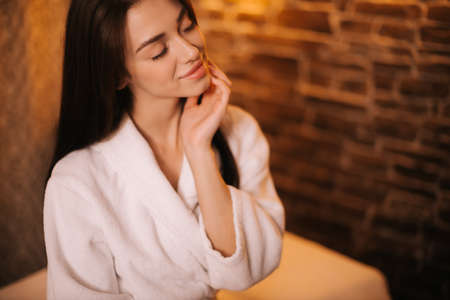 Close-up portrait of beautiful young female in white bathrobe with closed eyes on background of brick wall. Concept of luxury professional massage.