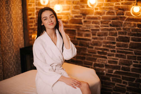 Beautiful young woman in white bathrobe sits on a massage table waiting for the masseur and looks into the camera, in spa salon with soft lighting. Concept of luxury professional massage.