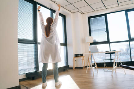 Back view of unrecognizable female doctor wearing white coat stretching hands on background of window in sunny day. Low-angle view of woman physician waking up in light modern medical clinic office