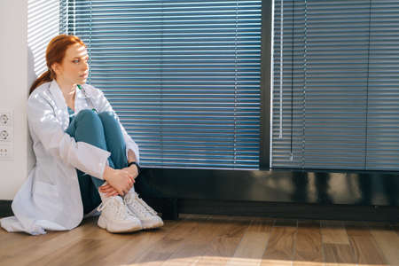 Depressed young female doctor wearing white coat sitting on floor hugging knees near window with love in light medical clinic office room. Unhappy woman physician depression feeling sad at hospital. Stock fotó