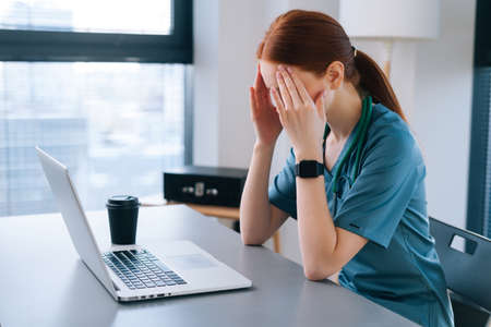 Side view of tired exhausted young female doctor in medical uniform having headache and rubbing head wiht hands, during working on laptop sitting at desk near window in hospital office of medic clinic Stock fotó