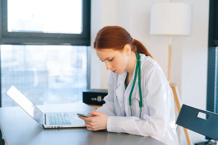 Front view of unrecognizable female doctor wearing white coat using mobile phone while sitting at desk with laptop on background of window in sunny day. Woman moving legs.