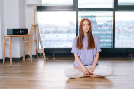Portrait of young relaxed woman meditating sitting on floor in lotus position on background of window in bright office room. Attractive redhead lady performing relaxing breathing exercises at home. Stock fotó