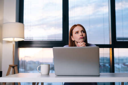 Front view of concerned redhead woman working on laptop computer looking away thinking solving problem at office. Focused lady using computer to study online work at home on background of window.