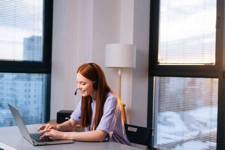 Side view of positive young woman operator using headset and laptop during customer support at home office. Sales representative at helpdesk talking with microphone and headphones near window. Stock fotó