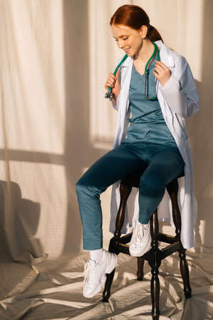 Portrait of smiling charming female doctor in white coat sitting on chair near window in sunny day in medical clinic office. Young redhead woman surgeon posing with stethoscope, looking down Stock fotó