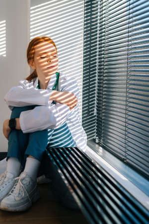 Close-up of disappointed sad young female doctor in white coat sitting on floor hugging legs with hands near window. Unhappy woman physician depression feeling worried about professional malpractice.