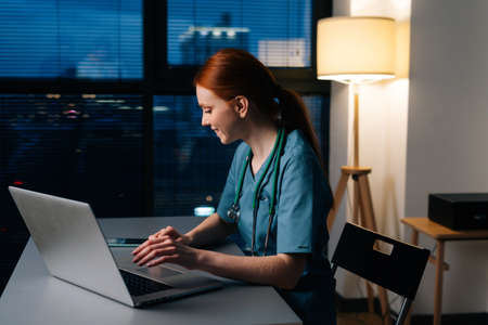 Side view of happy smiling redhead young female doctor in blue green medical uniform working typing on laptop computer, sitting at desk in dark hospital office room near window at night.