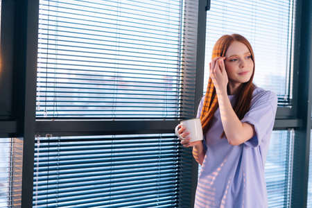 Attractive young redhead woman drinking coffee at home office standing near window after working day. Charming thinking happy female relaxing holding cup, drinking coffee or tea. Stock fotó