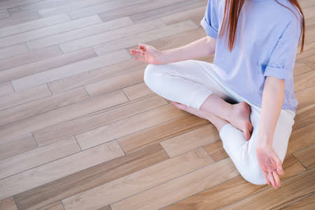 Top view of unrecognizable young woman meditating sitting on floor in lotus pose in light office room. Calm pretty redhead lady relaxation during yoga workout at home, barefoot.