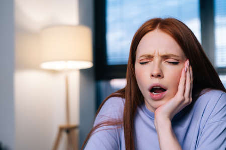 Portrait of tired young woman working typing on laptop at home office office, yawning feeling overworked and exhausted. Redhead lady workaholic yawning typing laptop keyboard, working late night. Stock fotó