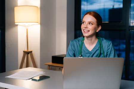 Cheerful young female doctor wearing blue green medical uniform typing on laptop computer looking away, sitting at desk in hospital office on background of window at night.