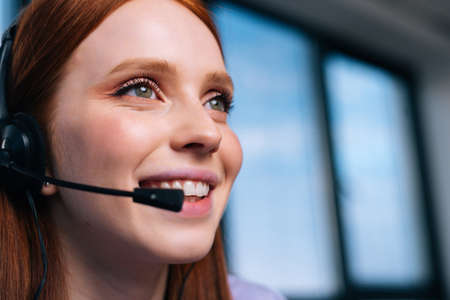 Close-up face of attractive young woman operator using headset during customer support at home office. Young redhead female student communicating online by video call on background of window. Stock fotó