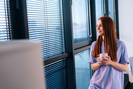 Happy redhead young woman drinking coffee standing near window after working day. Cheerful female watching sunset near panoramic window. Calm lady having rest with cup of tea.