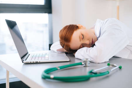 tired exhausted overworked young female doctor in white coat sleeping at desk with laptop and stethoscope on workplace. Close-up of woman physician seeing restless sleep