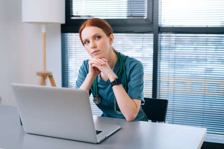 Portrait of thoughtful young female doctor in blue green medical uniform sitting at desk with laptop on background of window in hospital office of medic clinic, looking down. Stock fotó