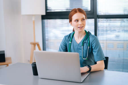 Portrait of positive young female doctor in blue green medical uniform typing on laptop keyboard sitting at desk on background of window, in modern office of medic clinic, looking away.