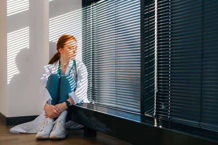 Depressed sad female doctor in white coat wraps arms around head sitting on floor near window. Stressed upset young woman physician feeling worried about professional malpractice
