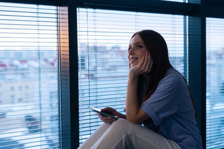 Happy redhead young woman dials number and speaks to boyfriend sitting on windowsill in evening after sunset. High-angle view of relaxed lady speaking phone with friends or family at home.